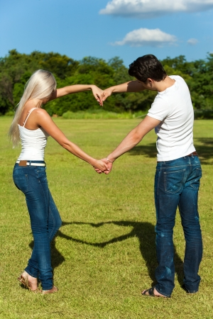 imitating: Portrait of young couple casting shadow of love symbol with arms.