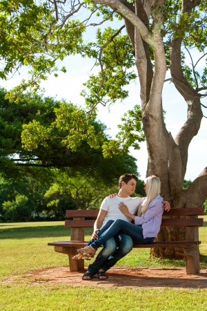 Portrait of young couple relaxing on wooden bench in park. photo