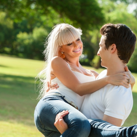 carrying girlfriend: Close up portrait of young man carrying girlfriend in arms outdoors.