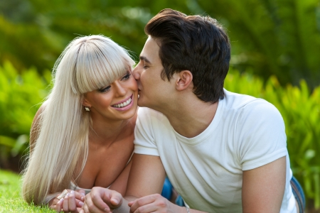 Close up portrait of young man kissing his girlfriend on cheek outdoors. photo