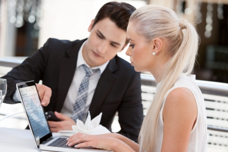 Close up portrait of young business partners reviewing work at lunch. Stock Photo