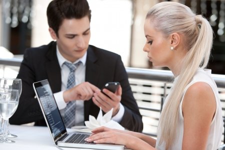 business dinner: Close up portrait of businesswoman working on laptop with colleague at lunch. Stock Photo