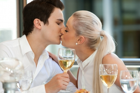 Portrait of cute young couple kissing at dinner table. photo