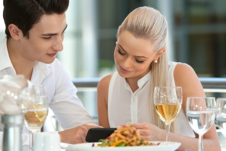 couple dining: Close up portrait of attractive couple looking at smart phone at restaurant. Stock Photo