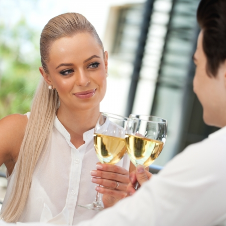 dinner couple: Close up portrait of attractive young couple making a toast with white wine.