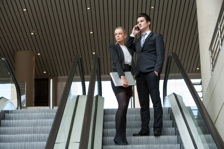telephone salesman: Young business colleagues going down on escalator.