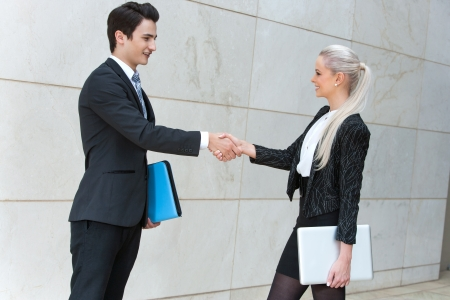 greets: Young business partners shaking hands over deal outdoors.