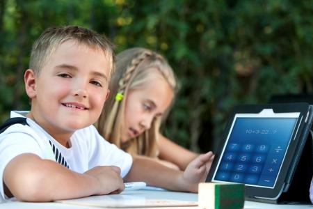 pre schooler: Cute boy student showing maths homework on tablet outdoors.