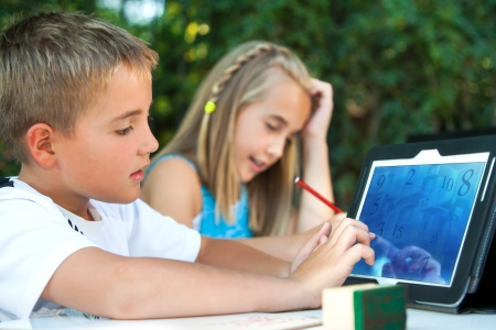 student desk: Cute boy student touching tablet screen outdoors. Stock Photo