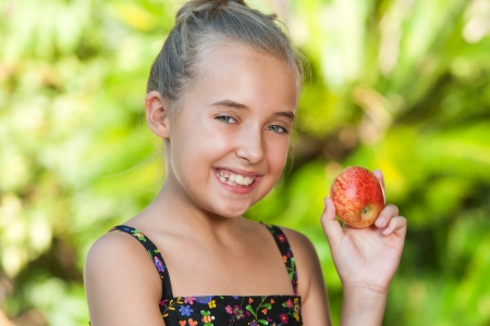 Close up portrait of cute girl holding red apple outdoors. Stock Photo - 18596964