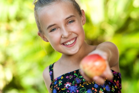 Close up portrait of cute young girl offering red apple outdoors. Stock Photo - 18596966