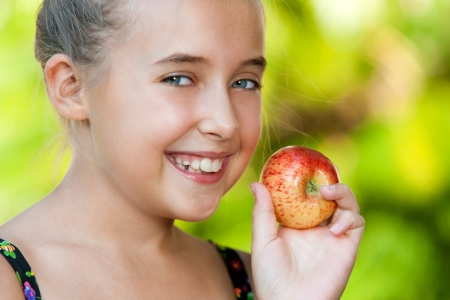 Extreme close up of cute girl holding red apple outdoors. Stock Photo - 18596965