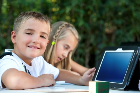 pre schooler: Portrait of boy student showing tablet with copy space outdoors.