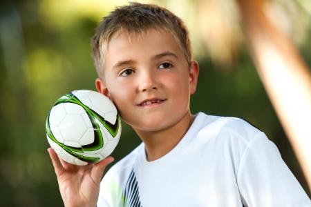 catching: Portrait of cute boy holding small handball outdoors.