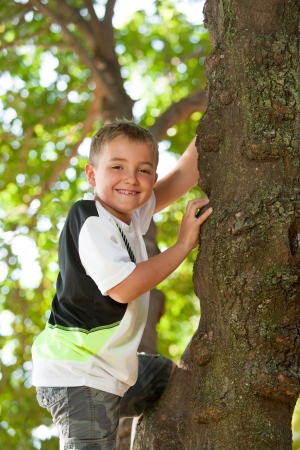 Close up portrait of cute boy climbing a tree. photo