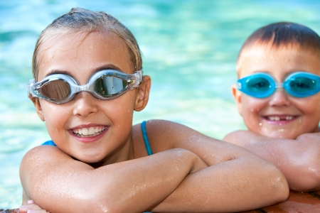 swim goggles: Portrait of two kids in swimming pool with goggles