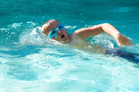 swim goggles: Small boy practicing in open air swimming pool.