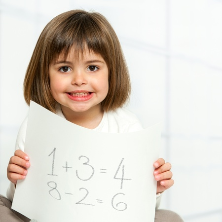Close up portrait of cute girl showing maths equations on paper. photo