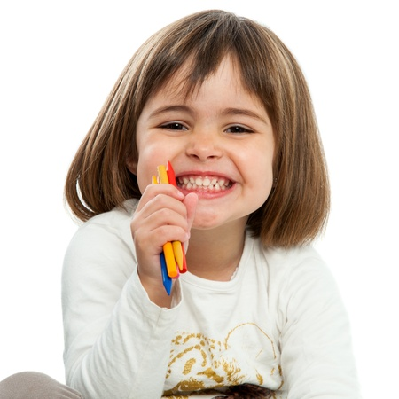 infant school: Portrait of happy girl with wax crayons.Isolated. Stock Photo