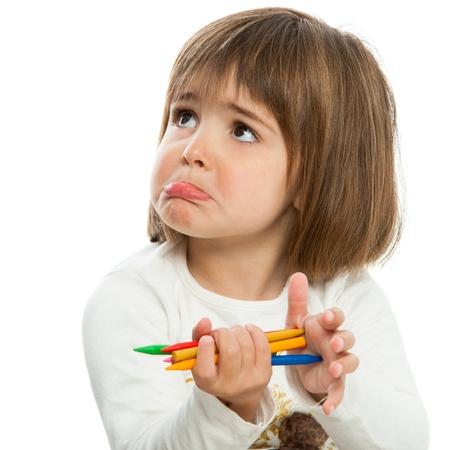 mirada triste: Cera infeliz niña que sostiene crayons.Isolated. Foto de archivo