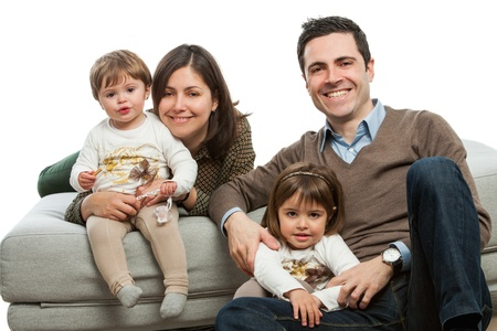 family on couch: Portrait of young parents with their daughters on couch.Isolated.