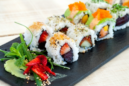 Close up of selection of uramaki pieces on black tile. Stock Photo