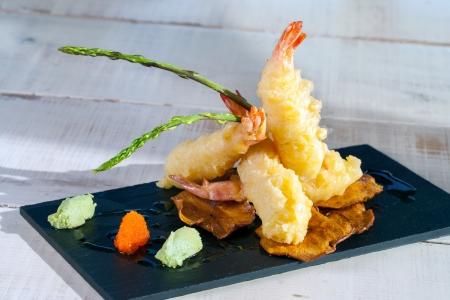appetiser: Close up of shrimp tempura appetiser served on black tile.