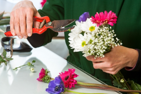 arranging: Close up of female hands pruning flower bouquet.