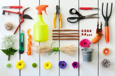 Primo piano di giardinaggio e fiorista strumenti su sfondo bianco in legno.