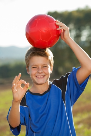 casualness: Young boy doing okay sign with red soccer ball on head. Stock Photo