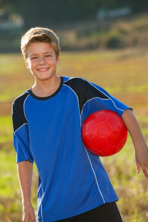 casualness: Close up portrait of cute boy with red soccer ball under arm.