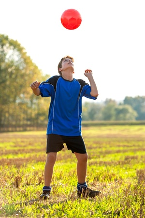 cute teen boy: Young boy in sportswear playing with red soccer ball outdoors.