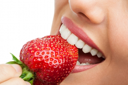 teeth smile: Macro close up of womans mouth eating strawberry. Stock Photo