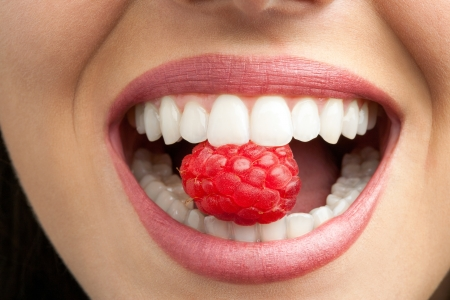 mouth close up: Macro close up of healthy female teeth biting raspberry. Stock Photo