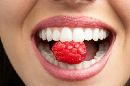 zuby: Makro zblízka zdravá žena zubů kousání malina.