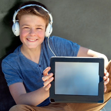 Close up portrait of cute boy showing blank tablet screen. photo