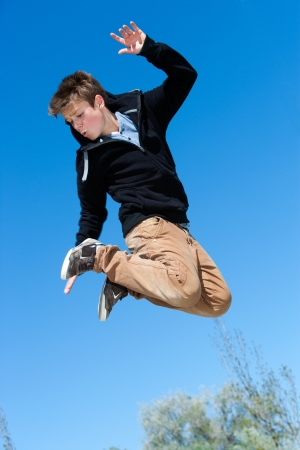 Close up portrait of energetic boy jumping outdoors. photo