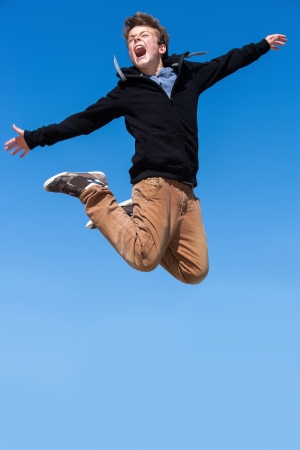 euphoric: Energetic boy jumping and shouting outdoors.