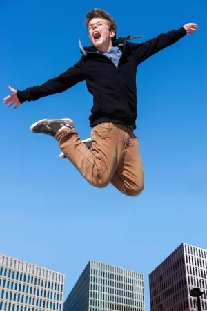Portrait of euphoric boy jumping high in city. photo