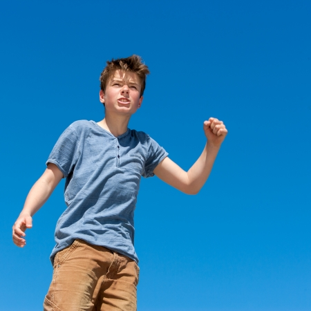 Close up portrait of upset boy raising fist outdoors. photo