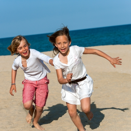 dynamic activity: Action portrait of boy and girl having fun on beach chasing.