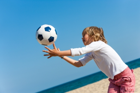 Close up action portrait of boy catching ball on beach. photo