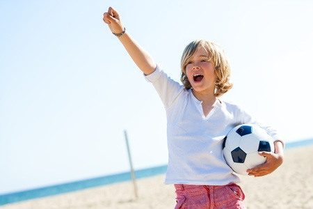 casualness: Portrait of boy standing on beach with soccer ball and winning attitude.