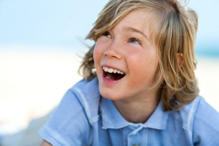pre adolescent boy: Close up portrait of laughing boy looking at corner outdoors. Stock Photo
