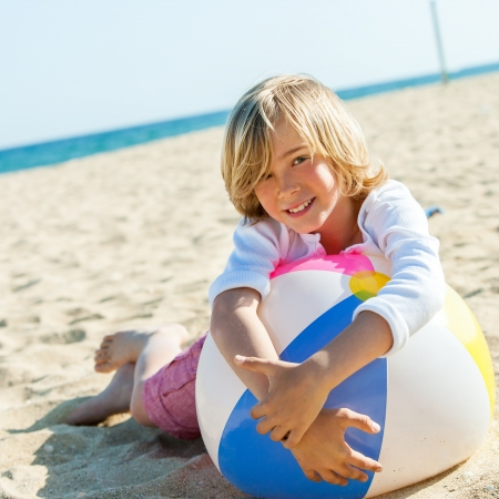 preteen boy: Close up portrait of cute boy laying on beach ball outdoors. Stock Photo