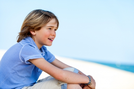 Close up portrait of cute boy staring at sea. photo