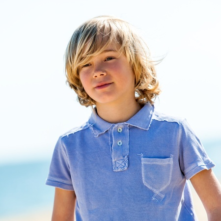 boy long hair: Portrait of cute boy wearing blue polo shirt outdoors. Stock Photo