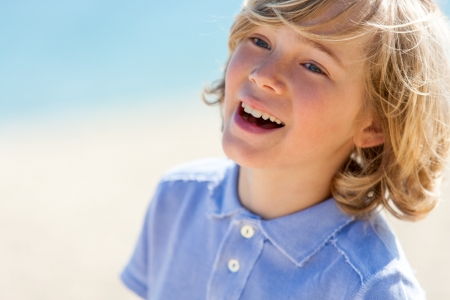 pre adolescent boy: Close up portrait of laughing blond boy outdoors. Stock Photo