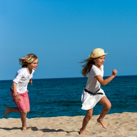 Two kids chasing each other on sunny beach. photo