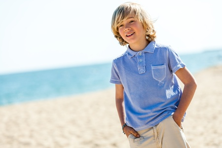 preteens beach: Close up portrait of handsome blond boy standing on beach. Stock Photo